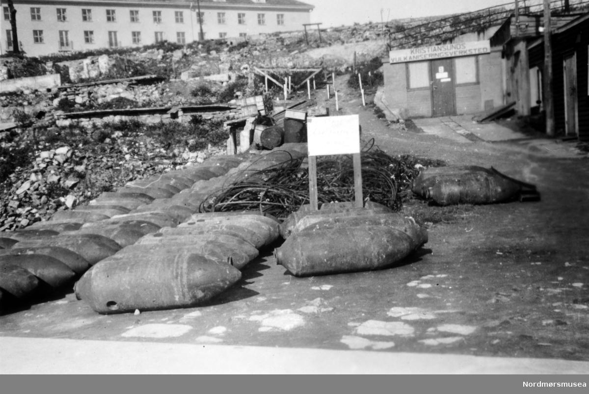 """Tyske flybomber ved Kristiansund Vulkaniseringsverksted. Tyske stridsvognsminer og personellminer hadde en helt annen utforming enn de flybombene som er avbildet. Det står """"miner"""" på advarsels-plakaten. Dette skiltet kan ha henvist til at tyskerne også minela området eller at de brukte mineskiltet som en generell advarsel. (Info: Johan B. Siira).  Miner var installert under Storkaia for å sprenge denne i luften ved en eventuell alliert invasjon av byen. Etter kapitulasjonen 8. mai 1945, ble disse minene tatt opp av tyskerne. I bakgrunnen ser vi nye Grand Hotell. Bildet er datert 20. mai 1945. Det står """"miner"""" på advarsels-plakaten.  Fra Nordmøre Museums fotosamlinger."""