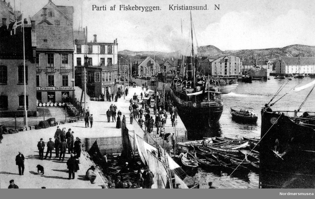 """Postkort med foto fra Fisketorget og Fisketrappa på Kirkelandet i Kristiansund. Som vanlig er det mye folk i gatene. Noen handler fersk fisk hos de lokale fiskerne nede i fisketrappa, mens andre venter på dampbåten som ligger ved kai. Vi ser fra venstre litt av tollbua/Toldboden med tollbodgjerdet til venstre. Deretter finner vi Jonas Eriksens Skipshandel, som per 2008 er å finne nær sakt på samme plass i dag 2011. Helt i bakgrunnen finner vi flere brygger. Fra venstre ser vi blant annet Johnsenhuken og Johnsenbryggen, mens til høyre ser vi Werringbryggen på Werringholmen, som i dag er en del av Devoldholmen. Kortet er stemplet """";Eneberettiget 1912. H. Werner's Kunstforlag, Bergen"""";. Piren, Fisketorget, Fisketrappen, Fisketrappa  Fra  samferdsel, mennesker, fiskebåter, robåter, Tollboden, Jonas Eriksen skipshandel,  Nordmøre Museums fotosamlinger."""