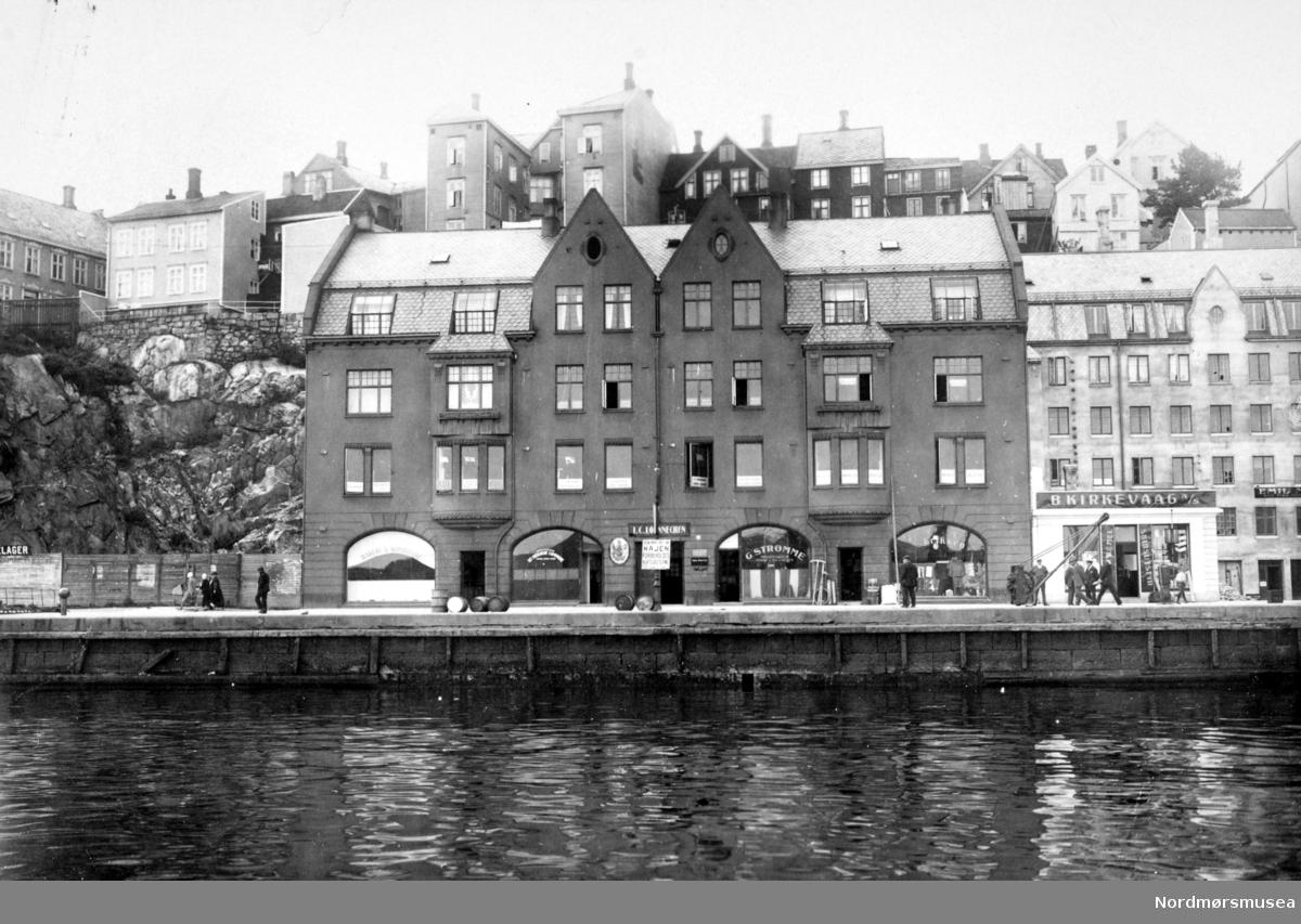"""Foto fra Loennechen gården i Vågeveien 7 (matr. nr. 1245). I. C. Loennechen ble etablert i 1926 og drev blant annet med dampskipekspedisjon, skipsmegling, assuranse, lager av bunkersolje og salg av kull med mer. Per 2008 holder blant annet Arkitektkompaniet Solem Hartmann og Unniform AS til i disse lokalene. Bildet er datert 1926  Merk at """";lamellen""""; (som det heter i Kristiansund) med skilt for Kirkevaag, ikke er et gjenreisningspåbygg, men var der på 20-tallet. Seinere Ripnes vesker etc.  Kolonialgrossist T Pedersen, sist TP Engros, før flytting til Løkkemyra: bare toppetasjen ble endret i 1940.  .   ALTØ: Lonnechens murgård ble oppført omtrent 1913/14. Bak plankegjerdet til venstre lå Greiff-tomta som ikke ble bebygd før krigen. Videre mot venstre ,utenfor bildet, ble Brødr. Dalls murgård oppførti i 1914 like etter Lonnechengården. Til høyre for Loennechegården- og bakenfor det lille hvite bygget lå firma Torstein Pedersens eiendom som ble totalskadd ved brann i 1913. Den nye murgården sto ferdig i 1915. Loennechen gården ble ikke ødelagt under bombinen i 1940. T. Pedersens bygg fikk store skader, men en del av murbygget ble benyttet ved gjenreisningen av bygningen. Lengst til høyre, utenfor bildet, lå den gamle gården som ble kalt Danholm-gården, antakelig var bygget omkring 1785 av de engelske kjøpmennene Isaac og Th. Moses. Den ble kalt for Danholmgården etter en senere eier Knud Danholm. Han hadde markert sitt eierskap ved å påmontere K. D oppe på husets ark. Eyvind Nisja kan fortelle at han far og en medeier, Husby & Eriksen, hadde motorverksted i underetasjen i Danholmgården. Det var på den tiden da bilene kom som deler i kasser og måtte monteres på verkstedene.  Se også foto og beskrivelse Kmb-1986-018.0033.  Bebbyggelsen i bakgrunnen lå i Hauggata og til Vågebakken der den krysset President Christies gate.  Det karateristiske huset med to arker, bak Loennechen-gården, var Hauggata 20.  Etter krigen ble denne tomta ikke bebygd og istedet ble det en utsikts"""
