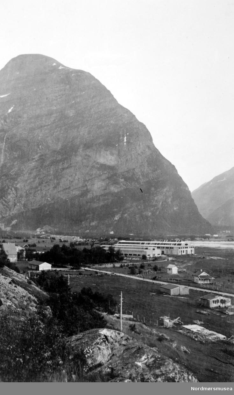 Sunndal verk nær foten av det svært så ruvende fjellet i bakgrunnen. Fotograf er trolig Georg Sverdrup, og datering er sannsynligvis fra perioden 1930 til 1939. Fra Nordmøre Museums fotosamlinger.