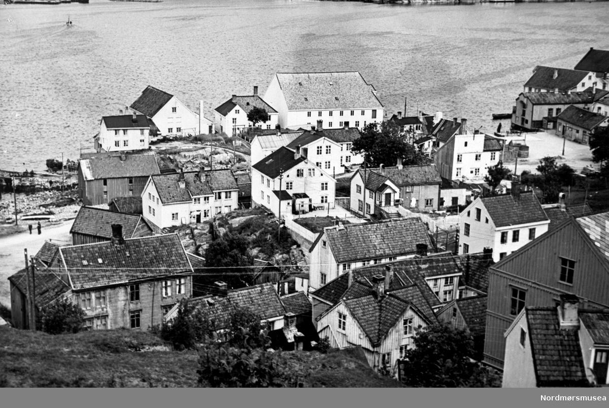 """Innlandet i Kristiansund ca 1920-30. """"Tahitibrygga"""" - Otterleibrygga, Fiskergt. 4. i midten, med sundbåtkai/allmenning til høyre, videre Tollbua og Dødeladen. Brygga ble bygd av Jonas Eriksen 1890, som saltlager.    Tidens Krav 17. desember 2019: Lanserer nye planer for Tahitibrygga.  Tahiti-Brygga AS, som er en del av Jebo-konsernet, ønsker å regulere og utvikle eiendommen til boligformål. Norconsult er innleid som konsulent, og Marco Böhm i Norconsult ber i det skriftlige planinitiativ om et møte med kommunen for å kunne sette i gang arbeid med regulering av Tahitibrygga.  – Formålet med planen er å legge til rette for boligformål med tilhørende utearealer med rundt 40 leiligheter, uteområder og bryggeanlegg, skriver Böhm.   Om tiltakets virkning utover planområdet, skriver Böhm blant annet at det vil være relatert til stedsidentiteten og bybildet på grunn av den kulturhistoriske verdien av Tahitibrygga og Innlandet ellers.  Tahitibrygga er preget av forfall og manglende vedlikehold. Ny bruk av den gamle saltlagerbrygga krever samvirke med det offentlige for å lykkes med bruksendringer og omreguleringer. Området går inn i hensynssone for bevaringsverdig bebyggelse med kulturell og historisk verdi på Innlandet.   Allerede under bryggemøtet på Dødeladen i sommer (2019) , signaliserte eierne av Tahitibrygga planer om å bygge boliger på eiendommen, som er en del av kjøpmannstunet sammen med Wirumbrygga og Wirumhuset på Innlandet i Kristiansund.  – Beliggenheten tilsier etablering av boliger i kjøpmannstunet, ved sundbåtkai og tett på havnebassenget. Ny regulering kan tilpasses et antall leiligheter som kan gi en økonomisk bærekraft og utnytte resten av området til gode formål, sa Kjell Oddvar Lervik i Jebo-konsernet i TK den 27. juni.  I planinitiativet går det fram at det ønskes å plasseres nytt leilighetsbygg mot Fiskergata og bak Tahitibrygga. Nødvendig parkering skal skaffes under bakken og i første etasjen, påpekes det i planinitiativet.  KJØPMANNSTUN: Byens sist"""