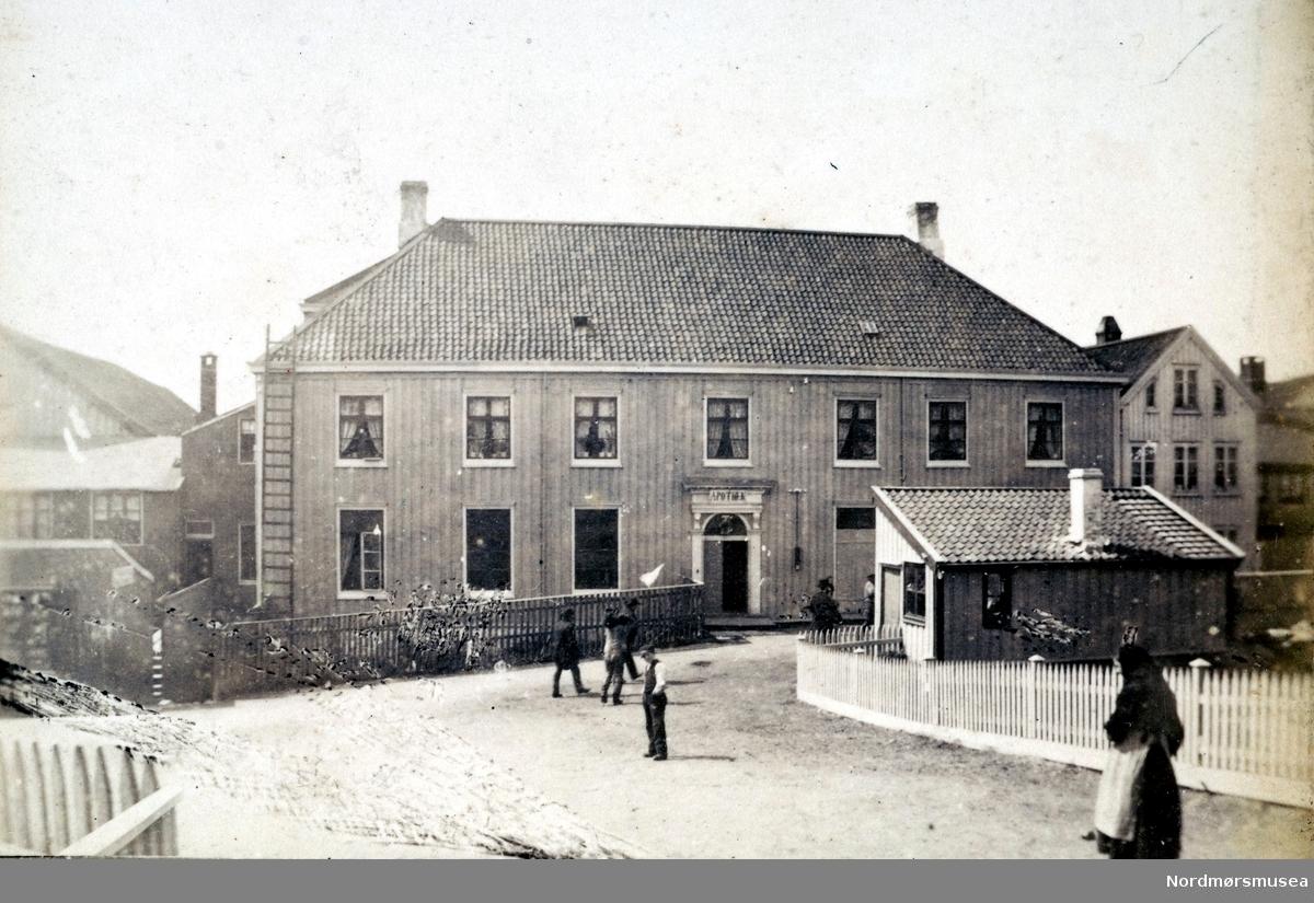 Bilde av en kjøpmannsgård, som senere ble til apotek. Kjøpmannsgården ble bygd av J. B. Clausen i 1813. I 1826 var gården kommet i Søren Knudtzons eie, for deretter å bli solgt til (ordfører?) H. H. Dahl i 1838. Senere ble kjøpsmanngården Nordlandets Apotek, som det er avbildet her. Bildet er datert 1883. Fra Nordmøre Museums fotosamlinger.