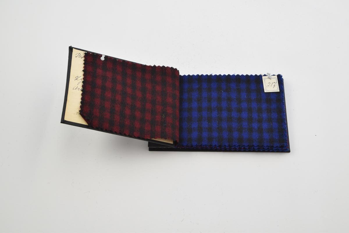 Prøvebok med 9 prøver. Tynne ullstoff med rutemønster eller uten mønster (monokrome) i røde og blå farger. Alle stoffer er merket med en firkantet papirlapp hvor nummer er påskrevet for hånd. Lappen er festet til stoffet med en stift/klype av metall.   Stoff nr. 216 (rød/sort rutet), 217 (blå/sort rutet), 218 (blå/sort stripet), 219 (rød/sort stripet), 391 (blå/sort rutet), 528 (blå), 529 (mørk blå), 530 (rød), 531 (mørk rød).