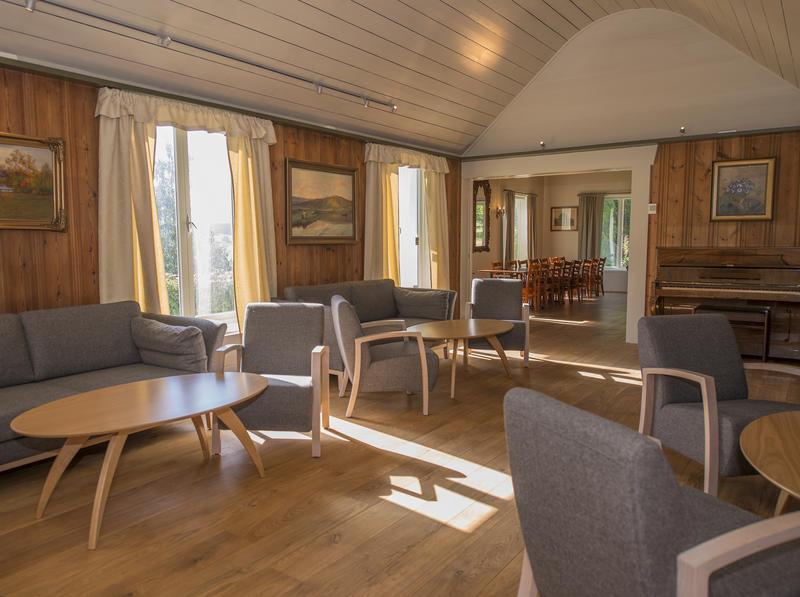 Salongen med piano og dobbelt skyvedør inn mot spisestua.
