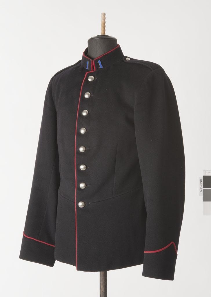 801087bc Mørk blå, enkeltspent uniform i ull med åtte knapper. Røde kanter.  Opprettstående krage