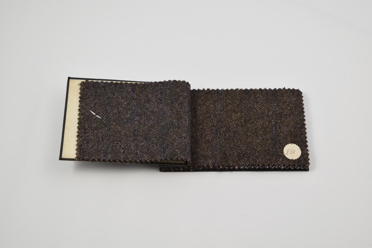 Prøvebok med 7 prøver. Middels tykke ullstoffer med diskret mønster, særlig striper, i blå og brune fargetoner.  Alle stoffer er merket med en rund papirlapp festet med melallstifter hvor nummer er påskrevet for hånd.   Stoff nr. 846 (brun), 848 (brun), 850 (brun), 852 (grå), 864 (blå-brun), 865 (brun), 866 (brun).