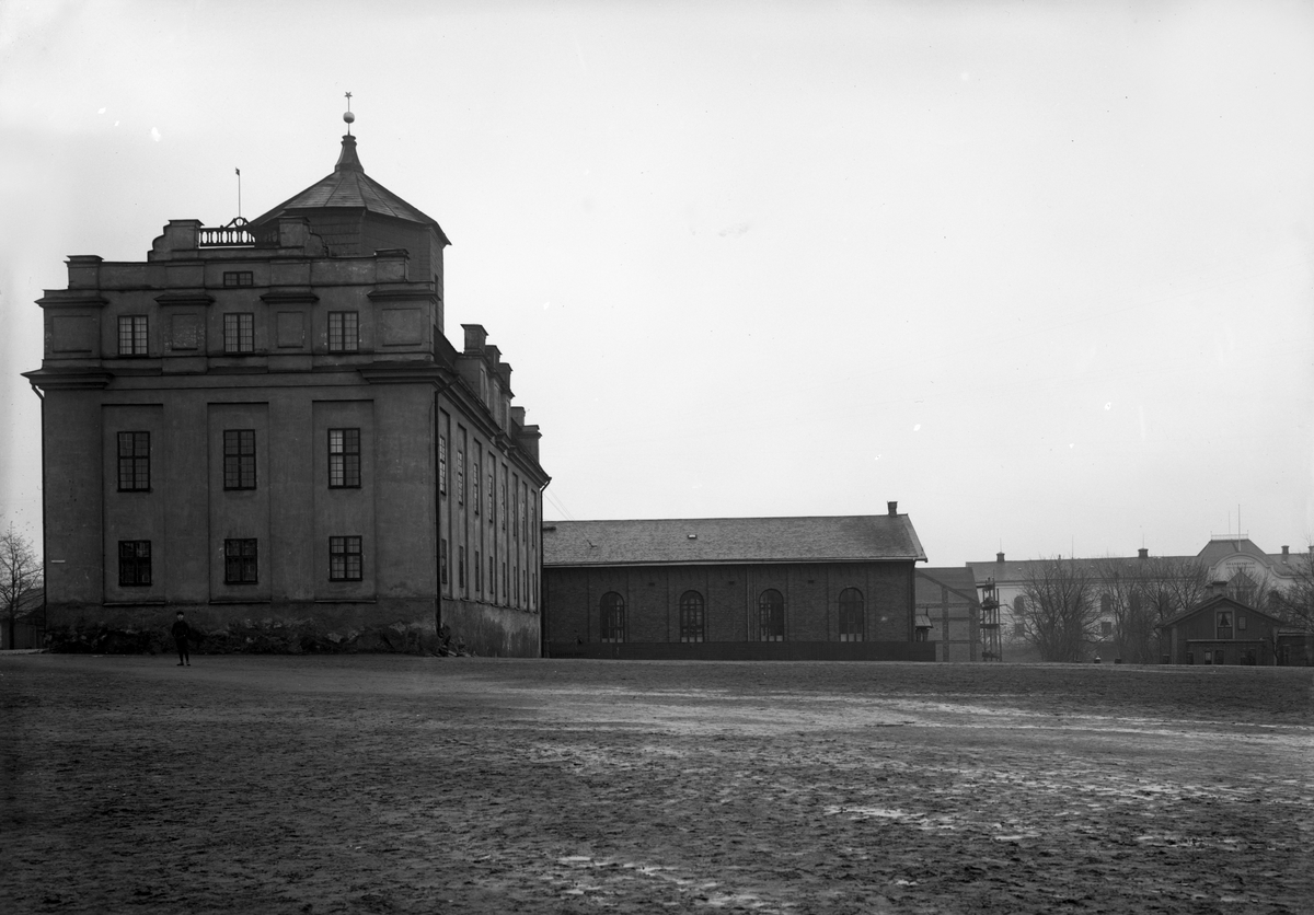 """Bild tagen vårvintern 1908. Annexet saknas och byggs några år senare och till vänster skymtar """"schatullet"""" som plockas ner inom kort och återuppförs på Herrhagen, okänt var. På tomten är Ludvig Martins nybygge, under lång tid med posten som hyresgäst, inflyttningsklart 1910. Läroverkets gymnastiksal är oputsad, saluhallen är under uppförande och den invigs 30 oktober 1909, gamla lasarettet används som brandstation sedan 1905 och villan till höger, traditionellt kallad """"bankens trädgård"""", ägd av översånglärare Lindh står kvar ett femtontal år och på den tomten invigs Baptistförsamlingens tabernakel 1925. Notera att skolgården är rena leråkern vid en blöt vår."""