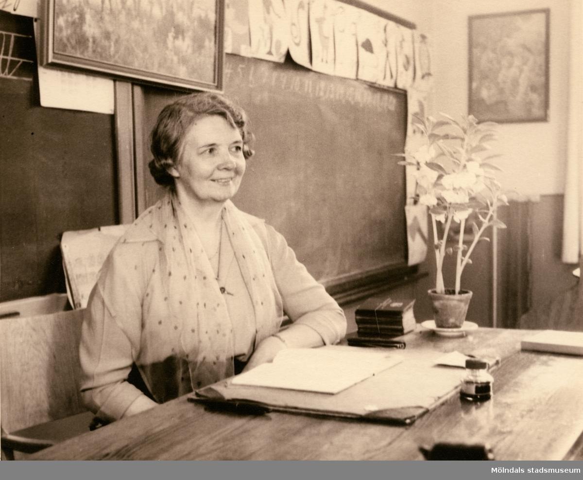Lärarinnan Agda Carlson vid katedern i Grevedämmets skola i Mölndal, ca 1950.  För mer information om bilden se under tilläggsinformation.