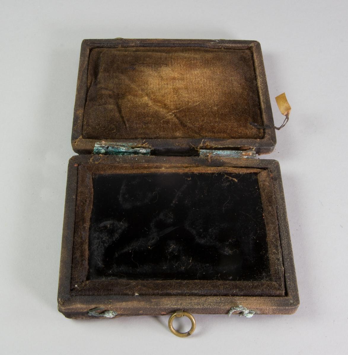 Svartspegel, enligt tidigare katalogisering. Troligen en dagerrotypi där motivet försvunnit. Rektangulärt glas, svart, monterat i fodral av läder klätt med svart präglat skinn. Runt glaset och invändigt i locket brun sammet.