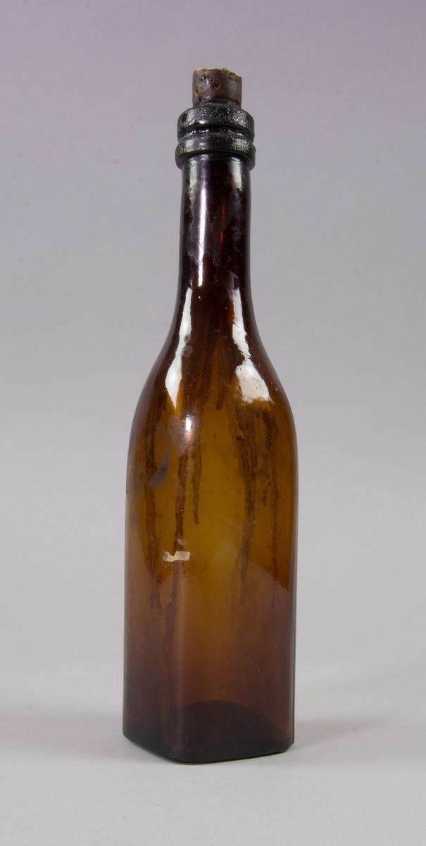 Flaska av brunt glas, kvadratisk, med kork.