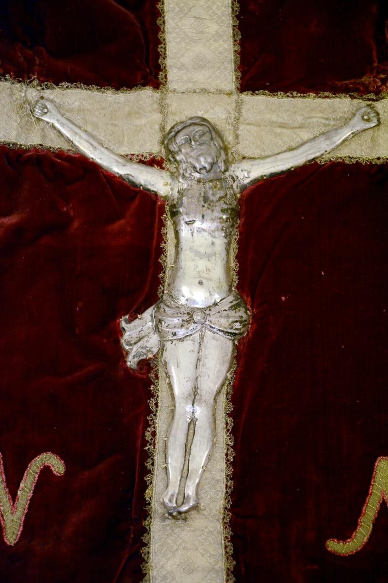 Kristus figur med armene opp i sølvrelieff. Montert på kors av silkebånd.