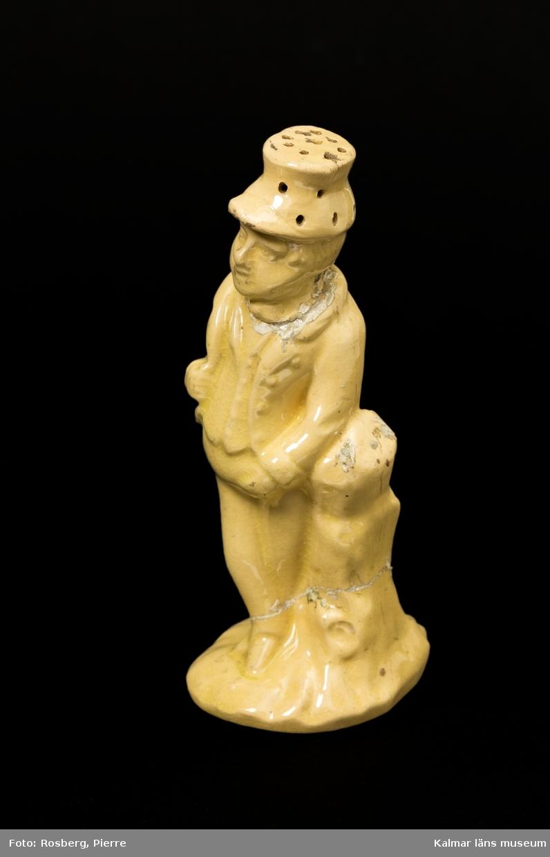 KLM 8871 Strödosa, peppardosa av keramik, gul skärv, klar glasyr. I form av en mansfigur med hatt, står vid en hög trädstubbe. I hatten ett flertal hål för funktion som ströare. Runt hål i botten för påfyllning. Datering, 1800-talets mitt.