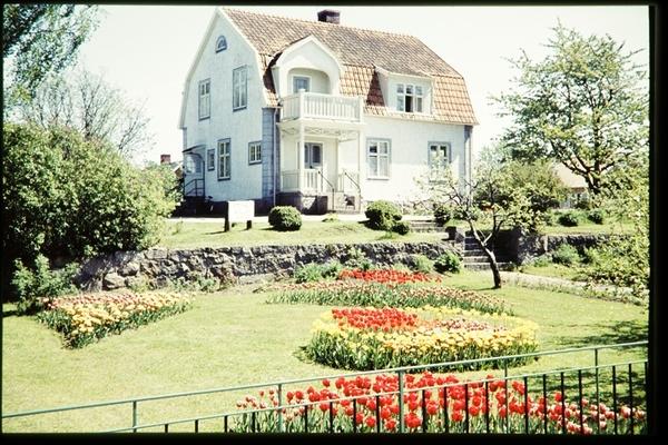 Trädgård växjö : Katolska kapellet i trädgården syns rabatter med tulpaner olika