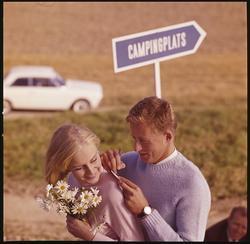 Par framför en skylt med text CAMPINGPLATS, i bakgrunden stå