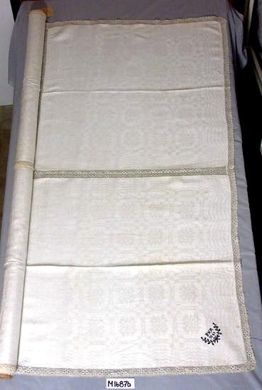 Duk, sydd av servetter, med knypplad spets. Vävda servetter i dräll, 6 st, 700 x 750 mm. Ihopsydda med en 35 mm bred, knypplad spets (naturfärgad) emellan samt samma spets runt duken.  Märkt: BHM 1869, samt en blomdekoration i korsstygn med mörkblått garn i ett hörn.  På motsatta sidan sytt likadant med monogram: AH 1949. En servett märkt med märkbläck: BHM 12.  Inskrivet i huvudkatalogen 1961.  BHM - Blända Helena Medin (1845-1926), f. i Moheda,  gift 1871 med Nils Gustaf Hörberg, Grimslöv Persgård - mor till Inez Hörberg. (AB). Funktion: Kaffeduk