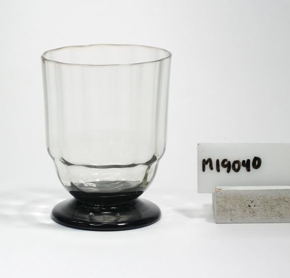 """Vattenglas/tumbler. Formgivet av Gerda Strömberg.  Ej identifierad servis. Eventuellt """"Black"""". Beskrivning: Cylindrisk med nedre delen klotsegmentformad, skivfot. Färg: Rökbrungrått klarglas. Foten svart, opak. Mått: Ovan anges höjd, övre diameter samt kupans djup.  Nedre diameter: 48 mm. Diameter fot: 52 mm.  Väggtjocklek: 1 mm. Kuphöjd: 65 mm. Inskrivet i huvudkatalogen 1966.  Kataloger: Se 1930 års katalog nr. 3281 """"Black"""". Funktion: Vattenglas"""
