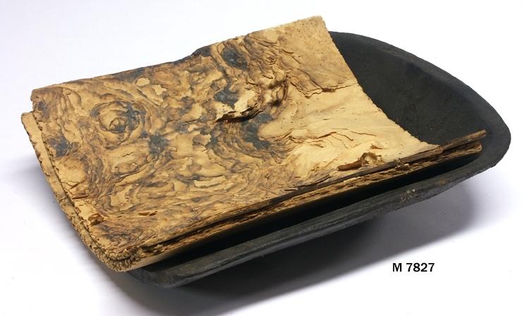"""Välsklump, eller """"kulklump"""", av järn bestående av  en i det närmaste rektangulär välvd """"vagga"""", som i  ena änden har en välvd """"vägg"""", medan andra änden  är öppen. I kulklumpen ligger två pappskivor. Kulklumpen användes vid fönsterglastillverkning. Efter  att man """"blåst hals"""" i välsklumpen (se M 7826) gick  man över till att forma själva fönsterglascylindern, genom  att kyla änden på ämnet och blåsa ut överdelen (under  halsen). Verktygets pappskivor blöttes före användning,  varvid man välsade fönsterglascylinderämnets """"botten""""  på desamma. När rätt diameter och tjocklek uppnåtts i  cylinderns övre del (i den andra änden var glaset massivt)  gick man över till att värma och slunga ut resten av cylindern. Invent. 2006-09-29. Inskriven i huvudkatalogen 1935. Funktion: Att välsa/forma glaset i inför uppblåsning"""
