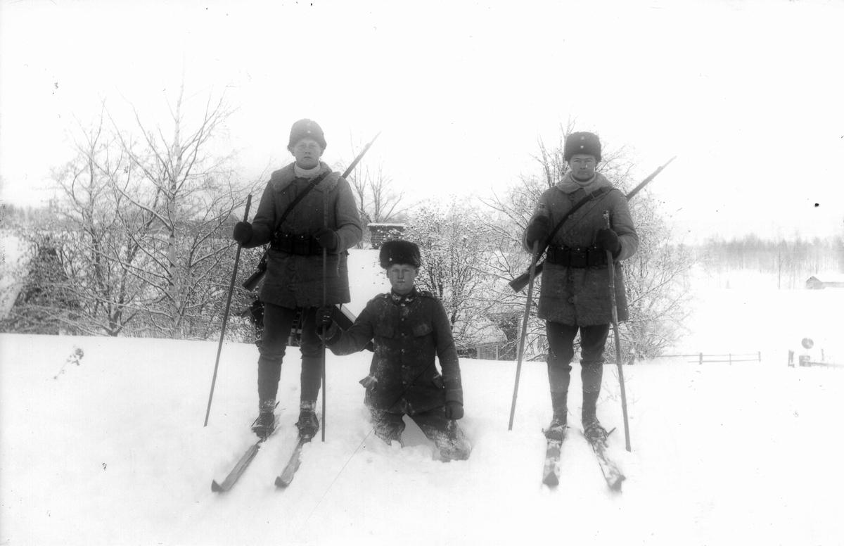 Militärer på skidor. Banvaktstugan strax bakom.