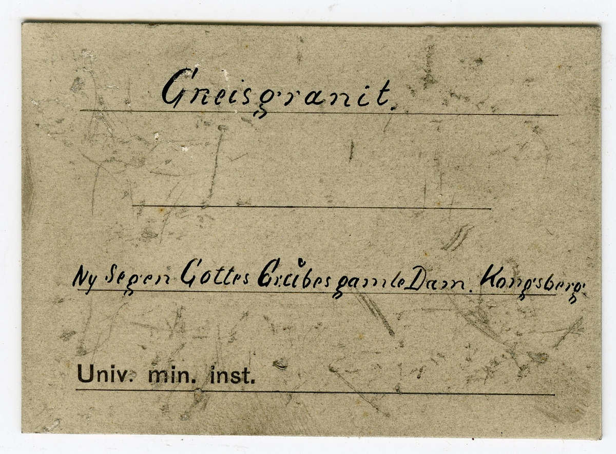 Etikett i eske: Gneisgranit. Ny Segen Gottes Grubes gamle Dam. Kongsberg.  + lapp