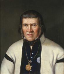 Portrett av Tallev O. Huvestad. Hvit trøye (jakke) og mørk vest kantet med rødt. Medalje hengende i kjede rundt halsen.