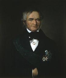 Portrett av Krohg. Mørk drakt, grønt ordensbånd, tre ordner.
