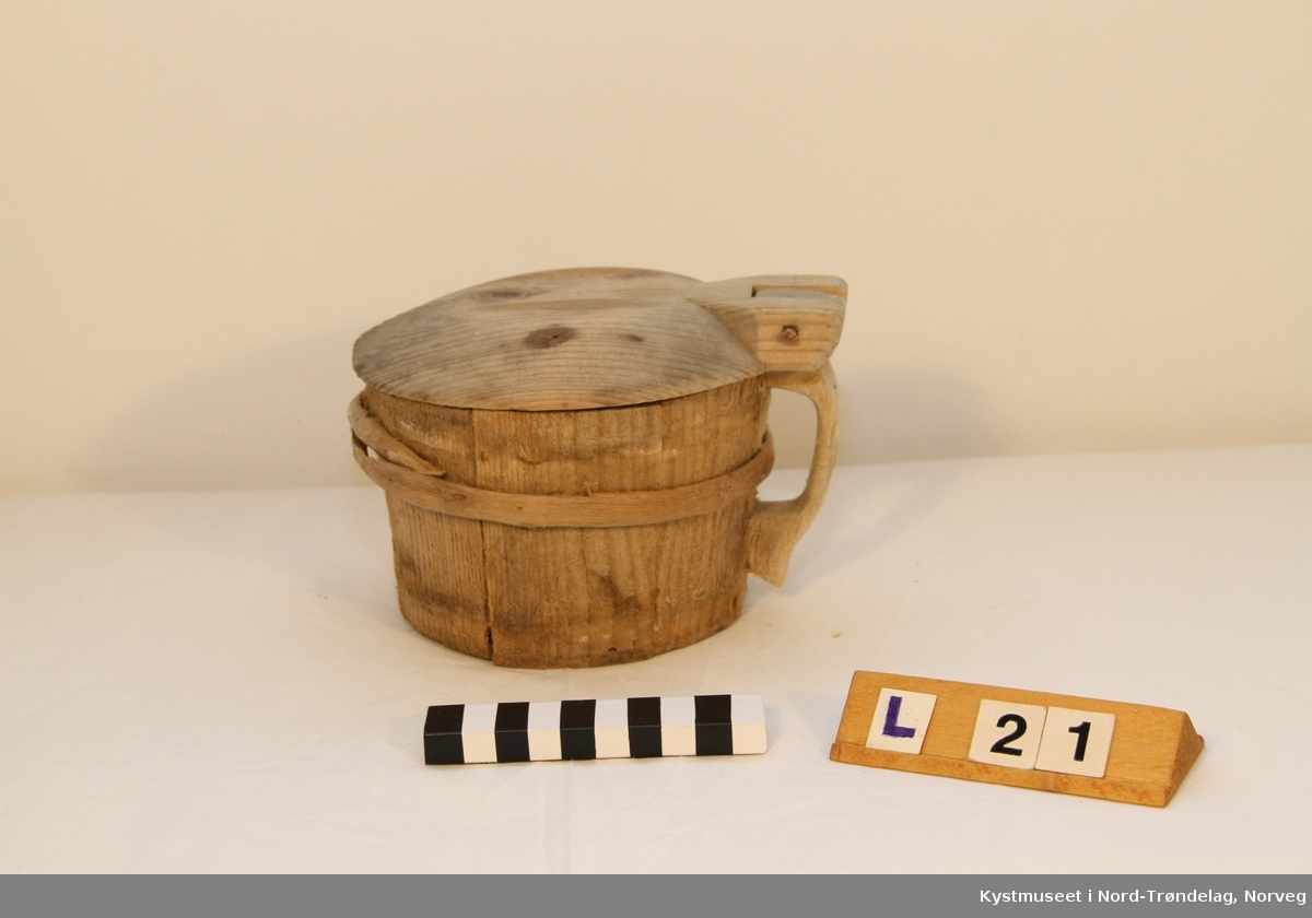 Smørkoppen er brukt til oppbevaring av smør. Treband; to nederst og et øverst. På lokke hank av jerntråd.