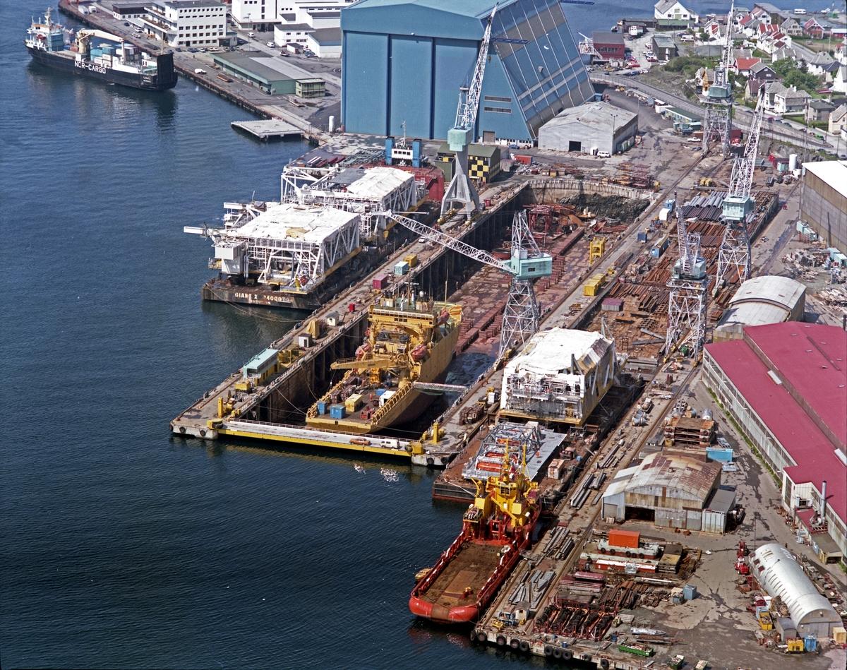 """HMV. Flyfoto. Moduler under transport ombord på """"Giant 2"""". Diverse andre moduler klar for transport. Skip i dokk og ved kai. Nordsjøhallen i bakgrunnen. Lastebåt fra Nordcargo ved Iglo."""