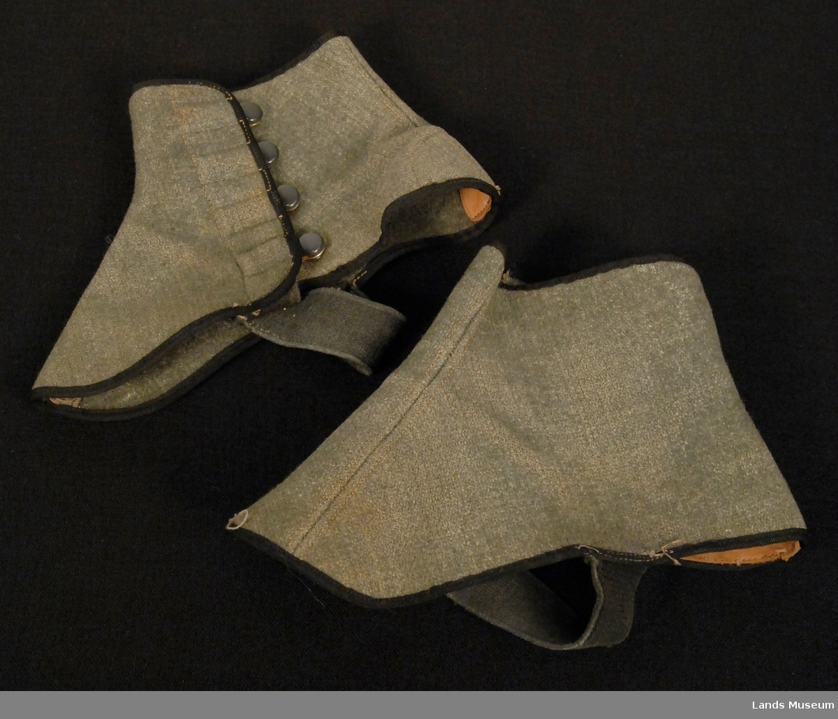 Herregamasjer med 4 knapper på siden. 1 par. strikk under foten. Svarte kanteband og knapper. Skinnforsterkning for hælen.