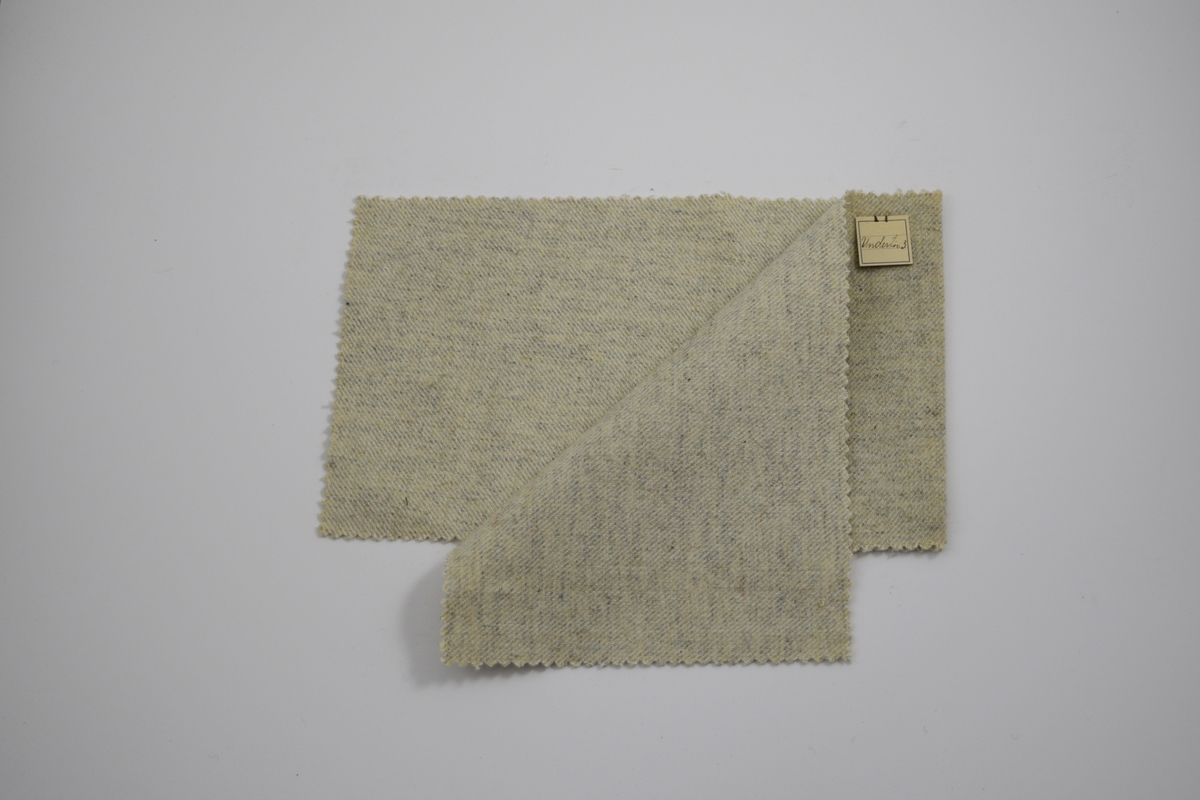 Stoffprøve klippet med sikksakk-saks. Middels tykkt ensfarget lysegrått stoff. Brettet på midten slik at formatet blir likt prøvene som finnes i prøvebøker fra Sjølingstad. Ingen merker etter å ha vært stiftet til bok tidligere. Stoffet er merket med en firkantet papirlapp, festet til stoffet med metallstifter, hvor stoffnavn er påført for hånd.   Stoff navn.: Undertói/3 (Alternativt: Undertøy/Undertøi).