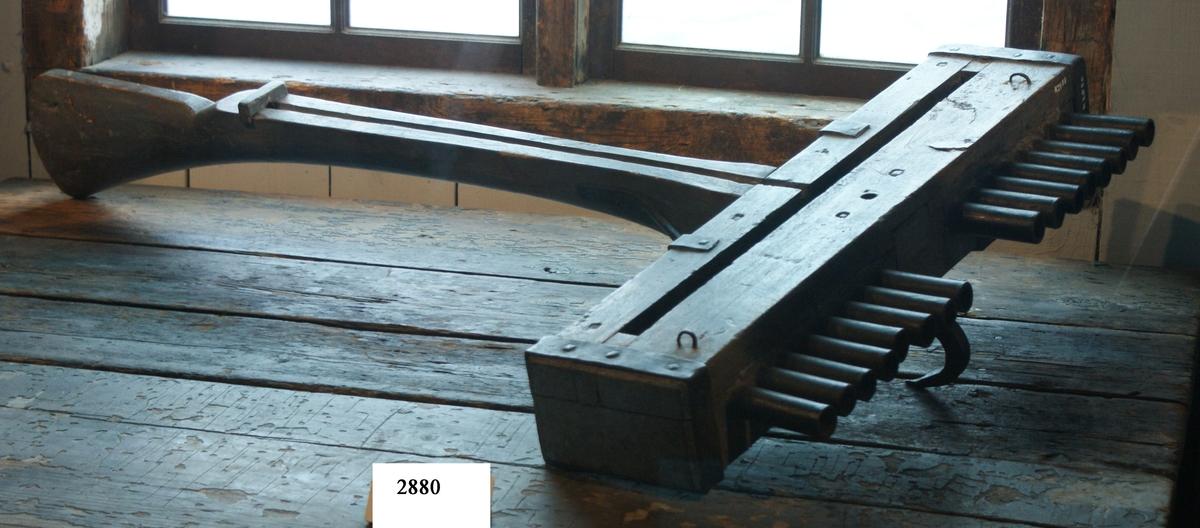 Skottbalk (orgelbössa).  Material: Trä med beslag av järn. Vapnet har 16 stycken pipor av järn. Från 1670-talet.