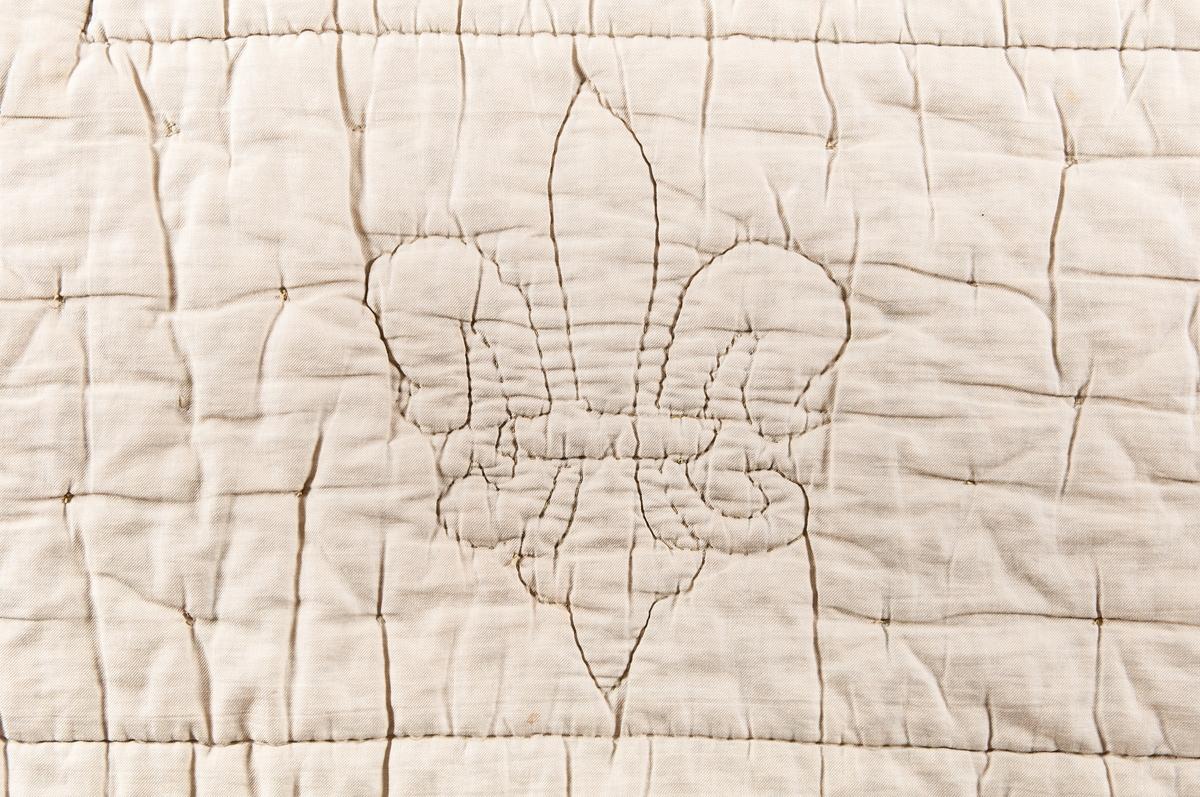 Sängtäcke av grönt så kallat täcksatin. Baksidan vit-beige. Stickat med mönster av franska liljan. Handsydda sidosömmar. Förmodligen stoppat med bomullsvadd.