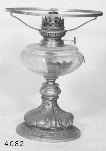 Bordslampa med gjuten fot av metall och fotogenhus av glas (spräckt). Utan kupa.