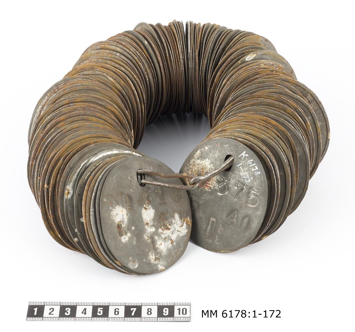 Bricka, kontroll-. Av bleckplåt. För arbetare vid Karlskrona örlogsvarv före 1918. Oval med hål för upphängning. Försedd med arbetarens nummer och daglön. (Endast 1 bricka märkt med inv. nr).