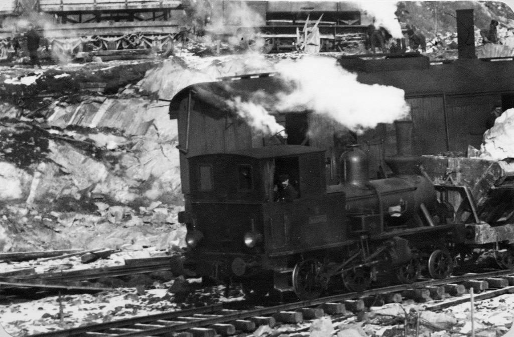 """Dette skiftelokomotivet hadde navn """"Bifrost"""". Loket fikk senere et LKAB-nummer 5.  Loket står nå plassert på Narvik stasjon.     Överst i bilden skymtar en treaxlig tippvagn och ett tidigare FLJ-lok. Därnäst en ångdriven grävmaskin samt Bifrost under växling av tippvagnar med dodbuffertar.     Dödbuffertar, tidigare vanligen skrivet dödbuffrar, är ofjädrade och förekom även på SJB schaktvagnar."""