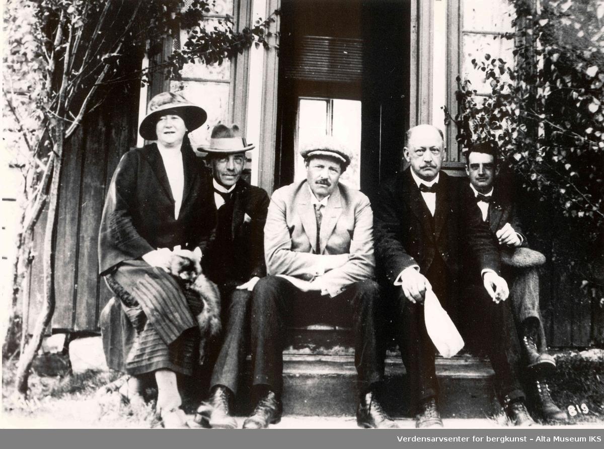 Fire menn og en kvinne sitter på trappen foran en trebygning.