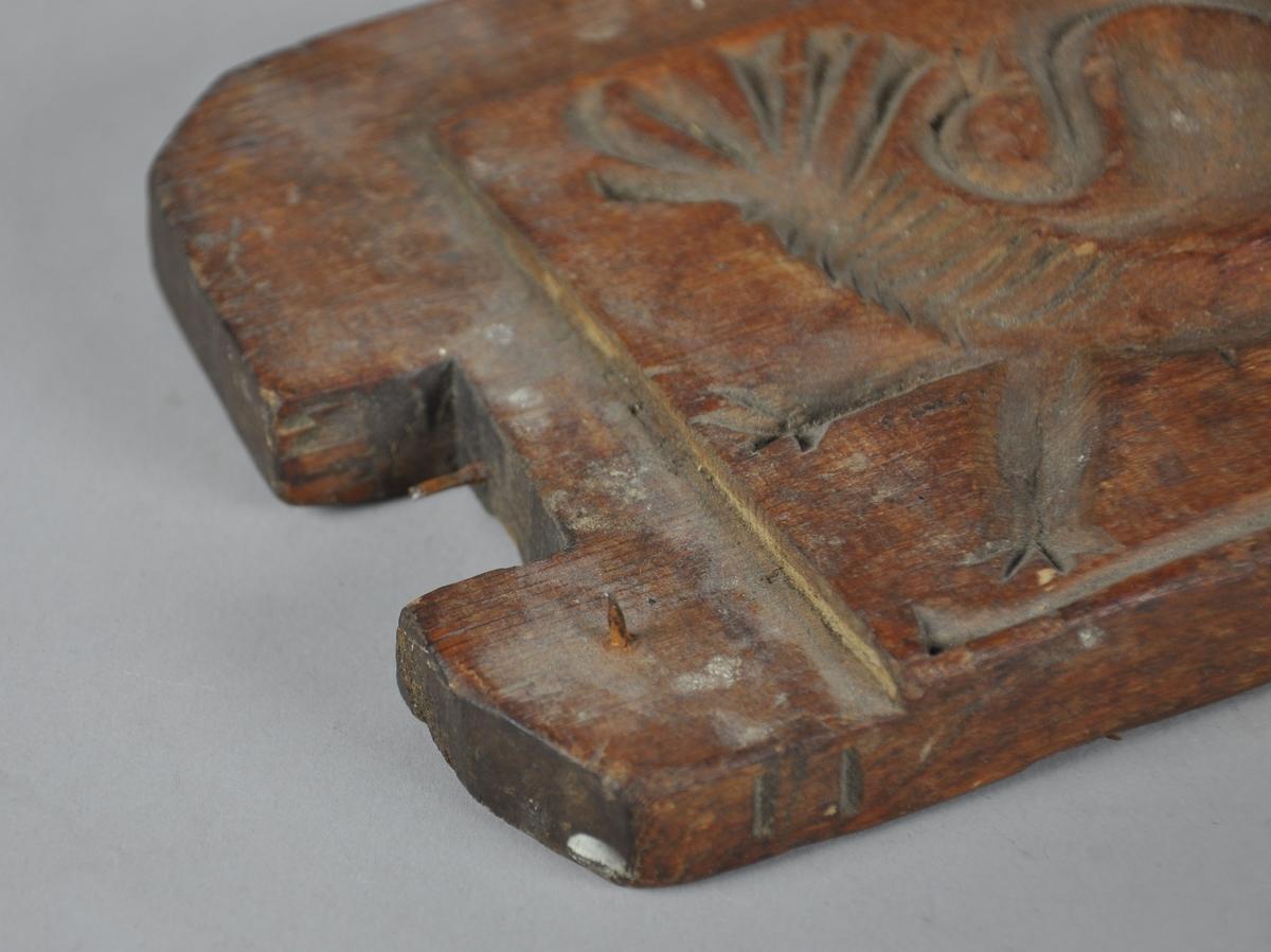 Sideplate til smørform, av tre. Støpeform på én side med motiv av abstrahert dyreform.  Formen har en liten, utstående spiker.