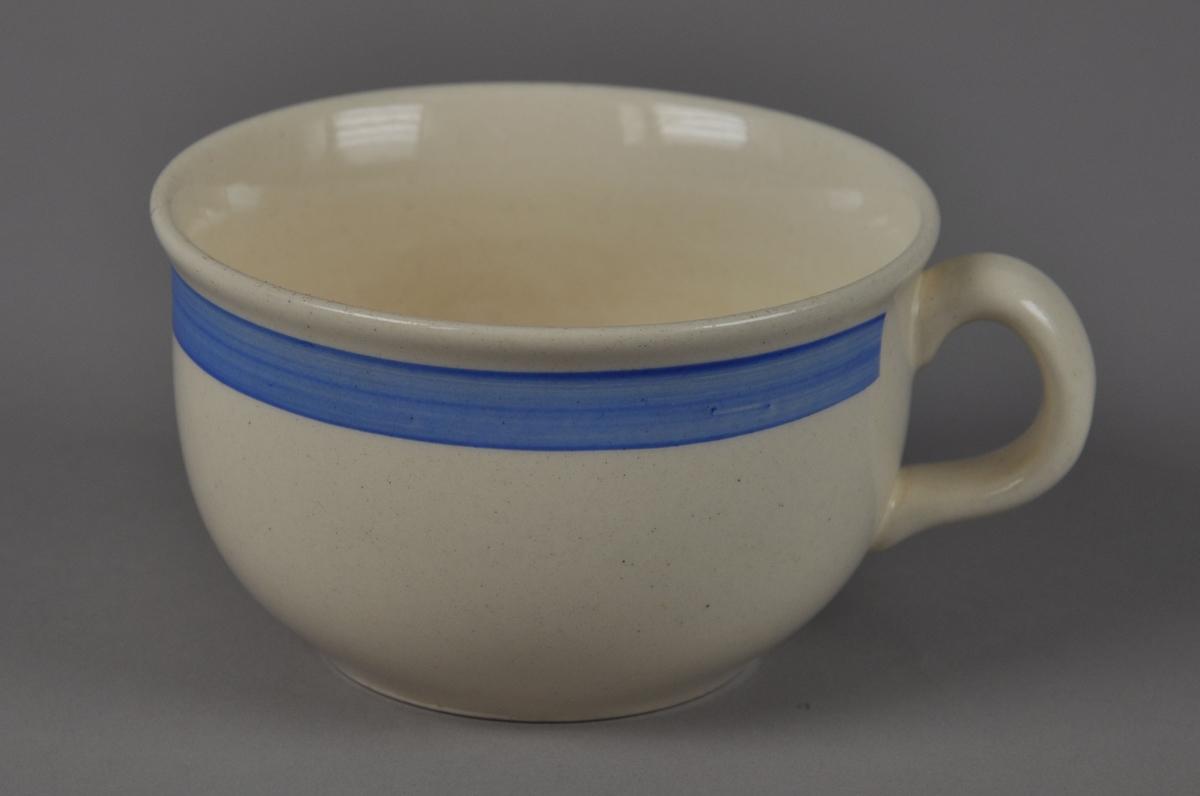 Kaffekopp av glassert keramikk, med hank. Koppen har en påmalt blå stripe rundt munningsranden.