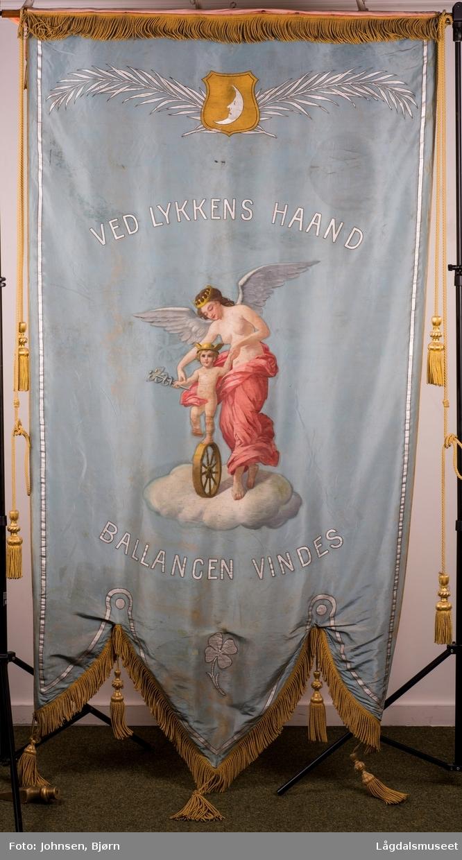 """Motiv s1: """"KONGSBERG HANDELSSTAND 1904"""" Avbildet på framsiden er Hermes (Romersk Merkur) som var i følge gresk mytologi gudenes budbringer. Derfor er han avbildet med vinger på hjelmen, og bærer en stav med vinger. Staven symboliserer balanse og harmoni. Nederst er det symbol for bergverk.  Motiv s2: Innskrift: """"VED LYKKENS HAAND BALLANCEN VINDES"""". Motivet i senter viser en engel og et barn. Øverst på fanens bakside er det en måne og bladranke. Nederst er det en firkløver."""