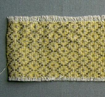 Vävprov i bomull och lin vävt i daldräll. Gallerliknande ytmönster i oblekt på gul tuskaftsbotten. Varp i oblekt/vitt bomullsgarn.Botteninslag i gult bomullsgarn, mönsterinslag i oblekt lingarn.