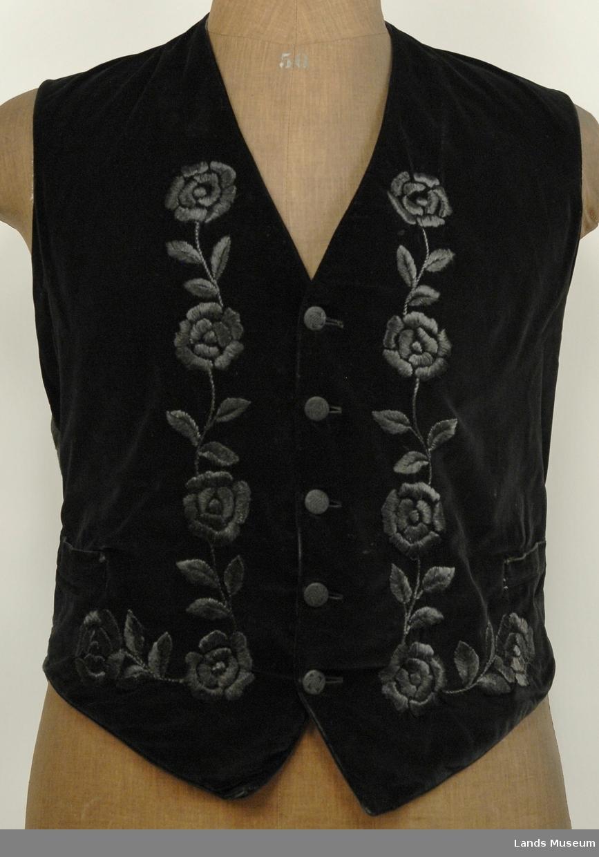Silkebroderi på forsiden i et rankemotiv, brodert i sort. 5 trekte knapper, sorte. 2 lommer.