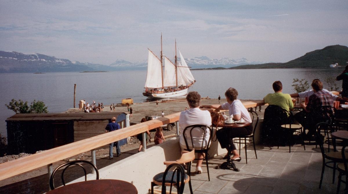 """Folk på terrassen utenfor Trondenes Historiske Senter. Anleggsbrakker og """"Anna Rogde"""" i bakgrunnen."""