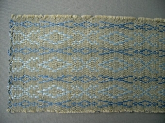 Vävprov, löparväv i bomull och lin vävd i daldrällsbindning. Blå och ljusblå bårder på grå botten. Varp i grått bomullsgarn nr 16/2. Inslag i olika nyanser blått lingarn nr 16/2 och 16/1.