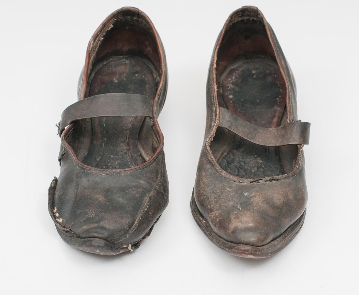 Sko i ler, høgrefot. Reim over rista, liten rund knapp til å feste reima i. Spiss tå, låg hæl. Sålen er plugga. Den er slitt med hol gjennom fleire lag. Skoen er også lappa på oversida. Er registrert  som berre ein sko, men den er svært lik ein sko i samlinga som tidlegare ikkje har hatt nummer eller er registrert. Har no nr. VFF 20057. Er fotografert saman med VFF 20057.