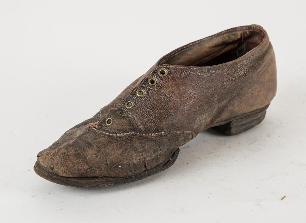 Sko, i brunt skinn med seks par maljer. Litt spiss. Heimelaga pluggsko. Liten hæl. Høgre fot.