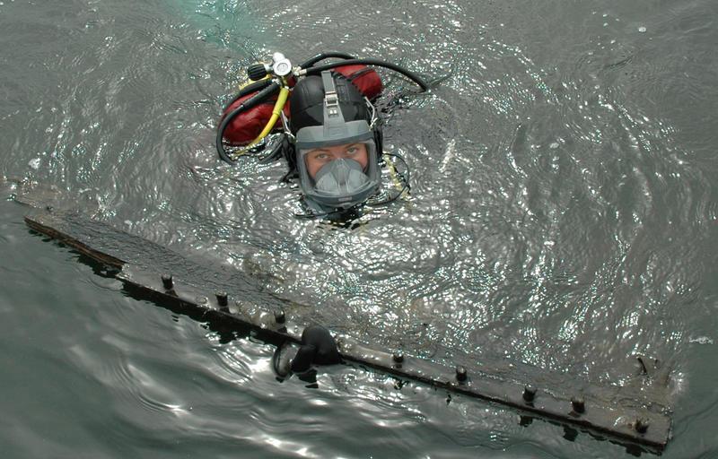 Dykker med båtdel i overflaten. (Foto/Photo)