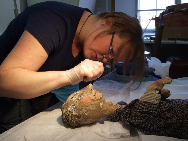 Gjenstandskonservator Helga Marie Stangeby renser ansiktet til en teaterdukke fra Asker museums samling. Foto: MiA