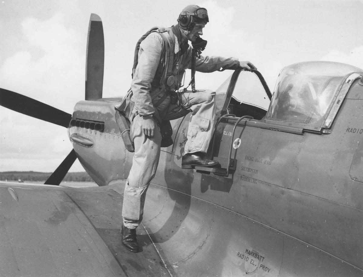 En man klädd i flygardräkt kliver in i flygplan S 31 Spitfire.