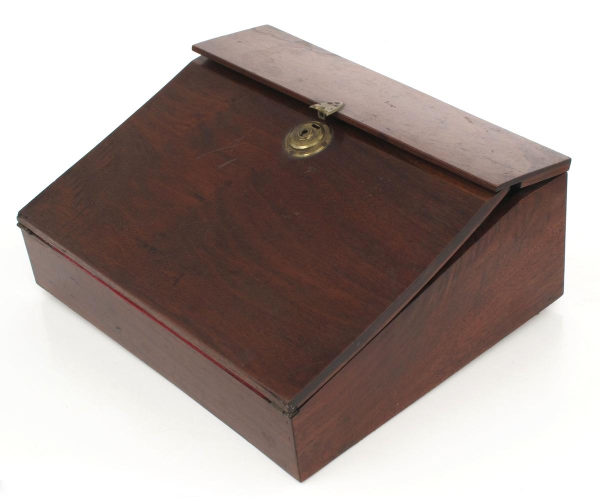 Skriveskrin. Mahogny. Skrin med rektangulær  bunnflate og skrått lokk. Øvre del av lokket er flatt og  åpnes bakover, den skrå del er skriveklaffen, som er kledd med rød filt. Bunnen under skriveplaten og innsiden av det skrå lokket er av furu. Under det smale flate lokk er to små rom på hver side av et  langt med buet treplate til penner.