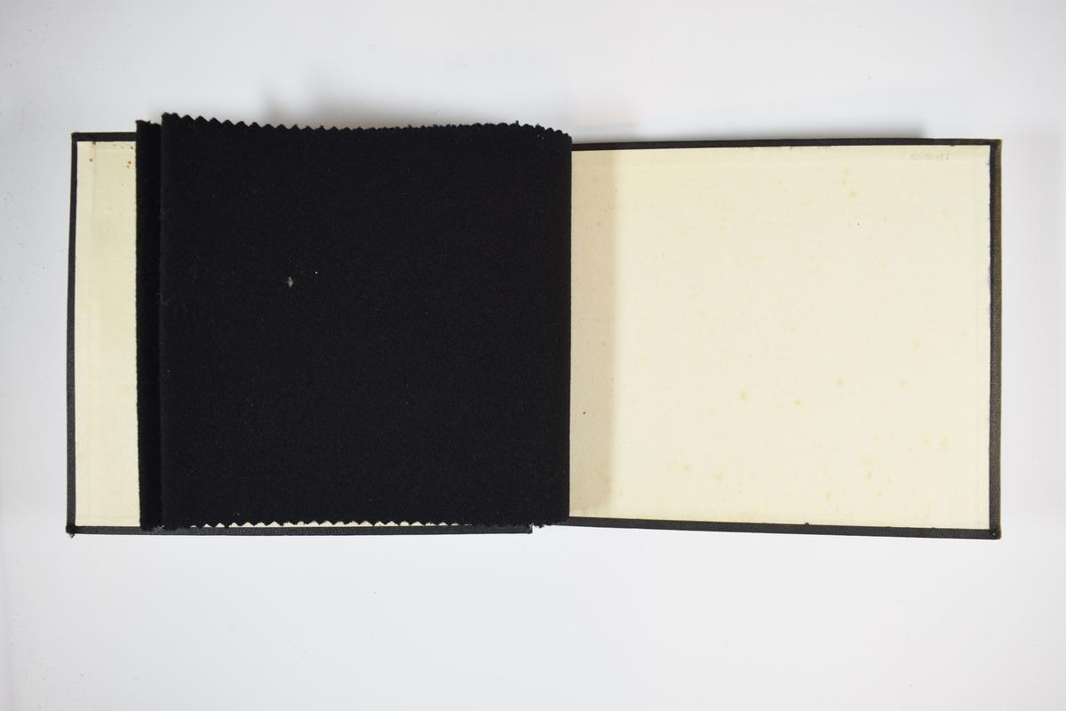Prøvebok med 2 stoffprøver. Tykke og kompakte ensfargede stoff. Stoff som har blitt valket/tovet, vadmel. Stoffene ligger brettet dobbelt slik at vranga skjules. Stoffene er merket med en rund papirlapp, festet til stoffet med metallstifter, hvor nummer er påført for hånd. Innskriften på det første stoffet indikerer at begge stoffene har kvalitetsnummer 199.   Stoff nr.: 199/1, 199/2.