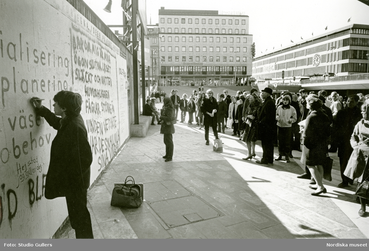 En man skriver på Klotterplanket vid Sergels torg, en kvinna läser vad som är skrivet på Klotterplanket. En folksamling tittar på dem.